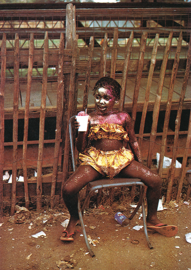 Little girl sits beside parade route in Trinidad